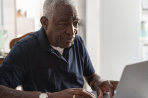 Older man working on a computer whole using Morphic's accessibility tools to make using his computer easier.