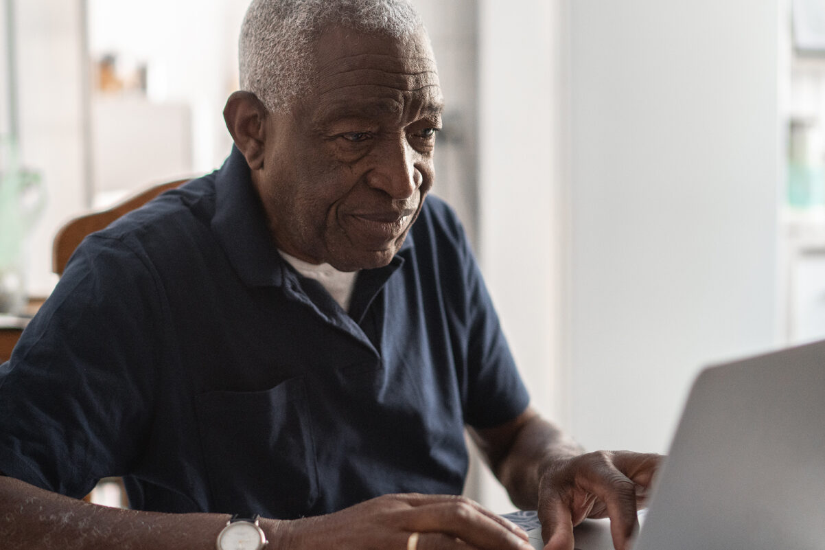 Older man working on a computer using Morphic's accessibility tool.