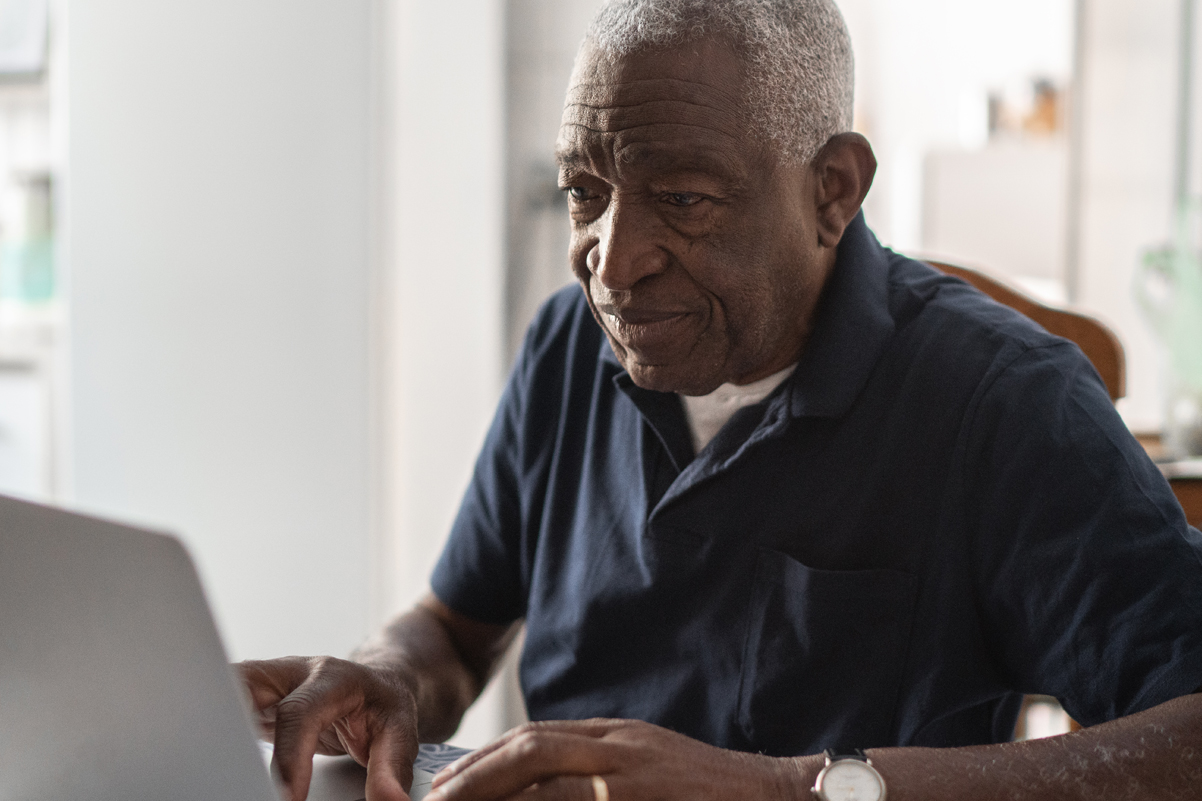 Older man working on a computer, using Morphic's accessibility tools.